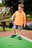 stock photo of miniature golf  - Young boy plays mini golf on putt putt course - JPG