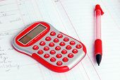 Red Calculator On A Notebook And Red Pencil