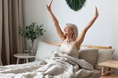 Happy Mature Woman Stretching In Bed Waking Up Happy Concept poster