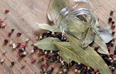 Dry Bay Leaf In A Glass Jar On A Wooden Table. Bay Leaf And Pepper Mixture Close Up poster