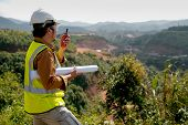 Engineer Manager Man With White Helmet And Hold Construction Paper Plan Use Fm Handheld Transceiver  poster