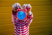 Preteen Boy Wearing In Red Shirt With White Stripe Holding Red Alarm Clock On Yellow Background, Chi poster