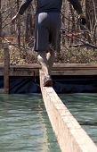 POCONO MANOR, PA - APR 29: A man walks across a narrow beam over water at Tough Mudder on April 29,