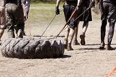 POCONO MANOR, PA - APR 29: A team runs on a trail dragging a large tire as an extra challenge at Tou