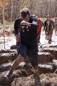 POCONO MANOR, PA - APR 29: A man runs through an obstacle with electrified wires at Tough Mudder on April 29, 2012 in Pocono Manor, Pennsylvania. The course is designed by British Royal troops.