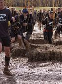 POCONO MANOR, PA - APR 28: A team runs through an obstacle with electrified wires at Tough Mudder on