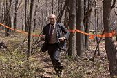 POCONO MANOR, PA - APR 29: A man in a business suit runs on a trail through the woods at Tough Mudder on April 29, 2012 in Pocono Manor, Pennsylvania. The course is designed by British Royal troops.