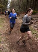 POCONO MANOR, PA - APR 28: Two women run on a trail through the woods at Tough Mudder on April 28, 2