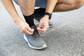 Man Runner Tying Running Shoes Before Run For Exercise In The Morning. Man Runner Checking Shoe In O poster