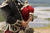 stock photo of bagpipes  - Scottish piper playing his bagpipes above Glengarry - JPG