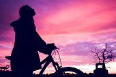 Chica con una bicicleta viendo el atardecer