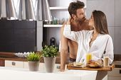 foto of bare chested  - Happy loving couple kissing in the kitchen in the morning - JPG