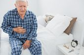 picture of belly-ache  - Elderly man suffering with belly pain in the bedroom - JPG