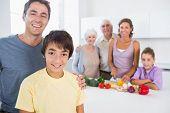 Vater und Sohn von Küchentheke mit Familie dahinter stehend
