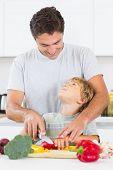 Vater und Sohn einander betrachten, wie sie Gemüse in der Küche hacken sind