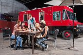 image of food truck  - Chef watching happy customers share pizza orders from food truck - JPG