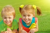 Photo of little brother and sister lying down on green grass field in sunny day, two adorable child playing on backyard, cute friends laughing outdoors in spring, preschooler kid, happy family concept