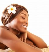 Picture of beautiful African woman with closed eyes enjoying dayspa, attractive female lying down on