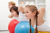 foto of gymnastic  - Kids and woman doing gymnastic exercises with balls  - JPG