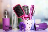 Hair brushes, hairdryer, straighteners and cosmetic bottles in beauty salon