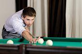 Man playing billiard. Spending free time on gambling