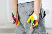 Little boy with hands painted in colorful paints hiding behind his back
