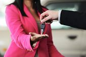 Woman buying a car and salesman handling keys