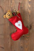Red Christmas stocking filled with a handmade teddy bear and gifts hanging by a rusty nail in an old