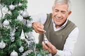 Senior man smiling while decorating Christmas tree at home