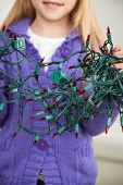 Midsection of girl holding tangled fairy lights at home during Christmas