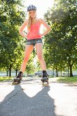 Casual smiling blonde standing hands on hips wearing inline skates in a park