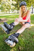 Casual gorgeous blonde wearing roller blades and helmet in a park