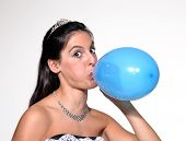 Funny bride blowing up a balloon.Woman inflating a balloon.