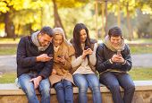summer, holidays, vacation, happy people concept - group of friends or couples with smartphones havi