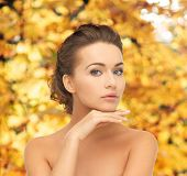 health and beauty concept - face and hands of beautiful woman with updo over yellow autumn leaves ba