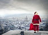Santa Claus over the city with red sack