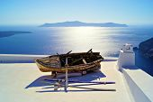 stock photo of boat  - Old wooden boat resting on the white rooftops of Santorini, Greece