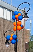 Colourful Balloons Adorn The Column With Lantern On A City Stree