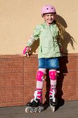 Little girl in a helmet and the protection of the hands and feet riding roller skates