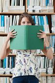 Portrait of a female student holding book in front of her face in the library
