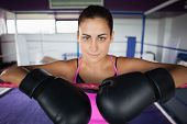 Close-up portrait of a beautiful young woman in black boxing gloves in the ring