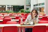 Portrait of a alone and sad female student sitting in the cafeteria with food tray