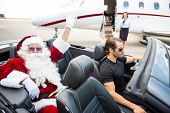 Portrait of Santa waving hand while chauffeur driving convertible with airhostess standing against private jet