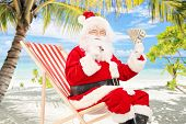 Santa claus on a vacation, sitting on a beach chair with cigar and us dollars, on a tropical beach
