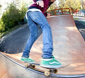 stock photo of skate board  - Skateboarder legs before jumping in the halfpipe - JPG