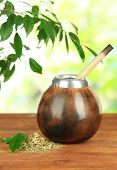 Calabash and bombilla with yerba mate on wooden table, on natural background