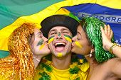 Group of multiethnic young adult fans celebrating victory of the Brazilian soccer team kissing each