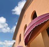 image of awning  - brown awning against a cloudy blue sky - JPG