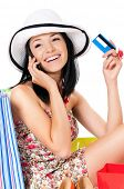 Shopping woman happy smiling holding credit card or gift card talking on cell phone, isolated on white background