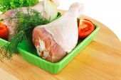 fresh raw chicken drumstick in green bowl ready to be baked on wooden plate isolated over white back